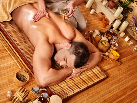 spa  thai massage: Man getting aroma massage in bamboo spa. Top view. Stock Photo