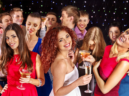 girl glasses: Group people with  champagne dancing at party. Girl dressed in red
