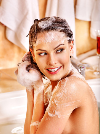 woman in bath: Woman relaxing at water in bubble bath. Girl looking to side.