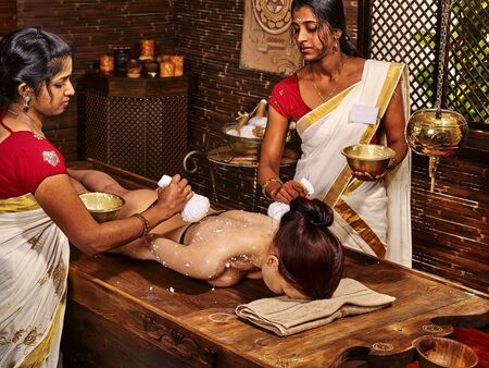 healing touch: Woman having ayurvedic massage with pouch of rice. Passage to India