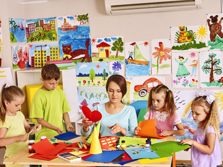 Happy children  with teacher at classroom. In background kids pictures Standard-Bild