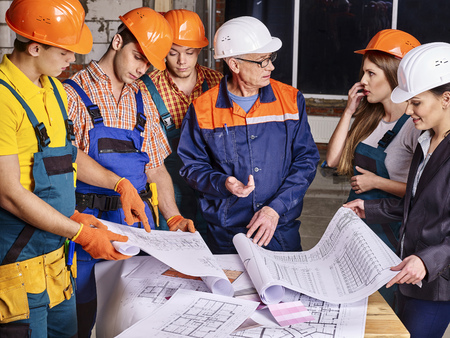 project manager: Business group people in builder helmet indoor. Drawings on table