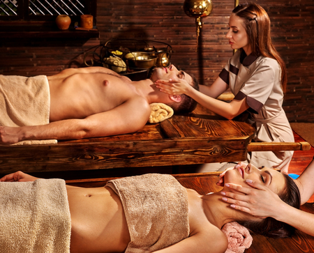 natural therapy: Couple  having oil Ayurveda spa treatment. Wooden table.