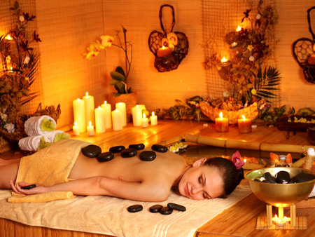stone therapy: Woman getting stone therapy massage in bamboo spa. Many candles.