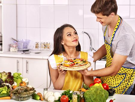 hombre cocinando: Joven feliz de pizza cocina familiar en la cocina. Mujer busca hombre.