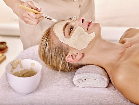 cosmetician: Woman with clay facial mask in beauty spa. Isolated. Plate on table