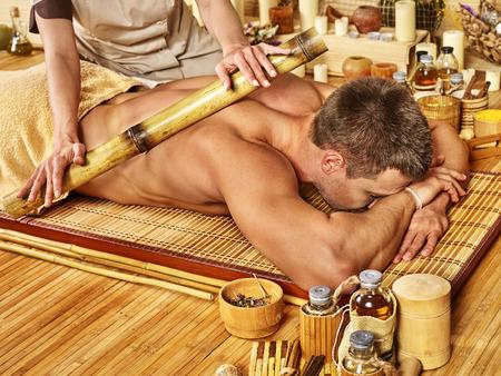 bamboo stick: Man getting bamboo massage. Female hand  therapist.Wooden floor. Stock Photo