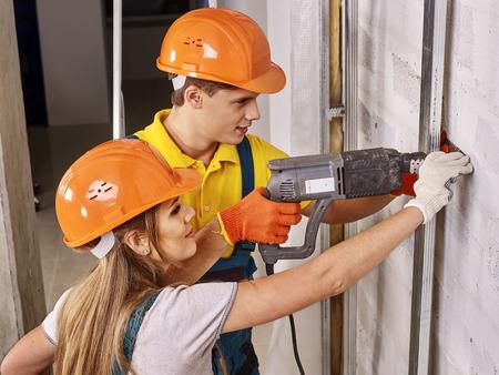 new construction renovation: Happy family in builder uniform indoor. Helmet on head. Stock Photo