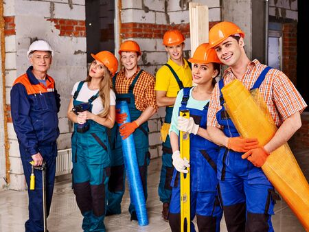 millwright: Happy group people in builder uniform. Senior man.