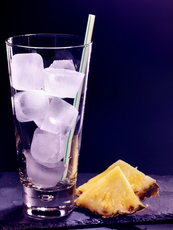 pilsner glass: Pineapplee drink on black background. Empty glass with ice cube .