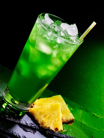 pilsner glass: Green pineapplee drink  with ice cube on dark background.