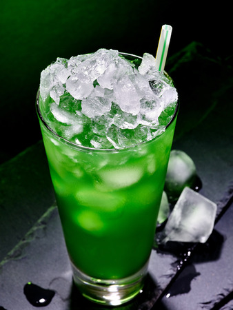 crushed ice: Green drink  with crushed ice on dark background.