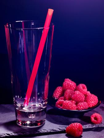 pilsner glass: Raspberry drink on black background. Empty glass with straw. Stock Photo