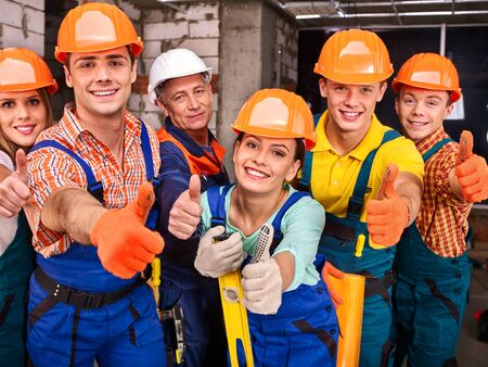 millwright: Happy group people in builder uniform thumb up.