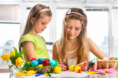 creative egg painting: Children girl paint Easter eggs at home. Flowers in basket.