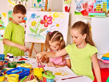 maestro: Ni�o pintura en caballete en la escuela. Maestro ayuda.