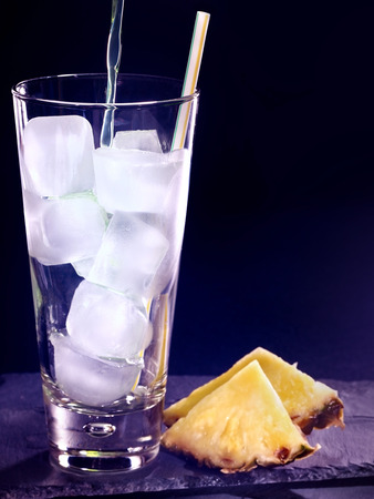 pilsner glass: Pine applee drink on black background. Empty glass with ice cube .