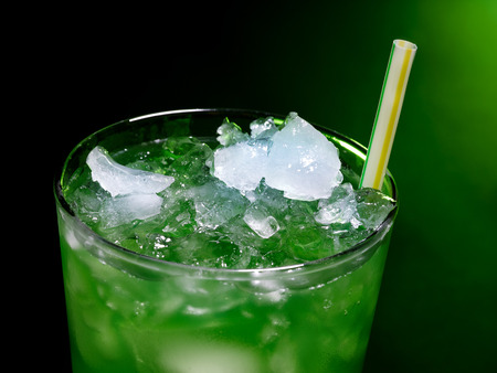 Green drink  with crushed ice on dark background. Top view. photo