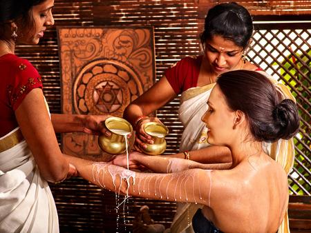 body milk: Woman having Ayurvedic spa treatment. Pouring milk.