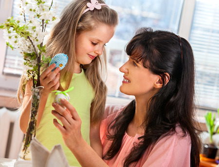 Happy family with child hang easter egg.Mother and daughter. photo