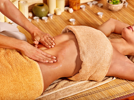 Junge Frau bekommen Massage im Bambus-Spa.