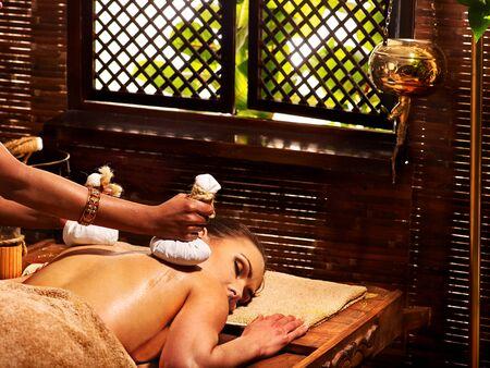 window treatments: Woman having Ayurveda massage with herbal ball.