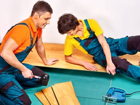 laying: Happy men laying parquet at home.