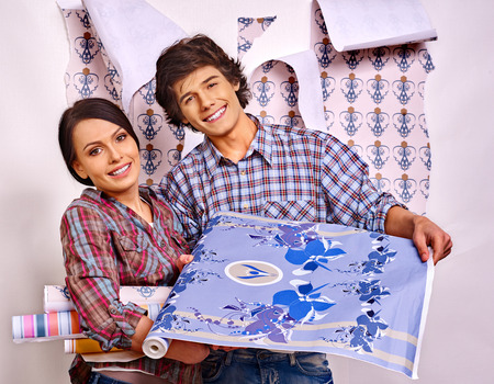 home decoration: Happy family glues wallpaper at home.