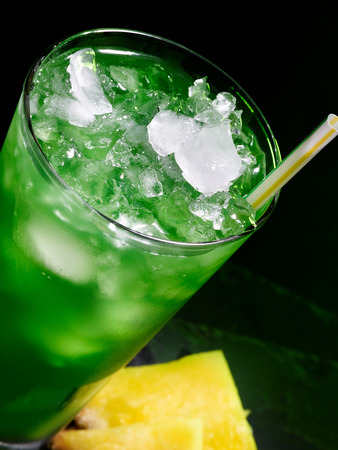 tilted view: Green drink  with crushed ice on dark background. Top view. Glass tilted