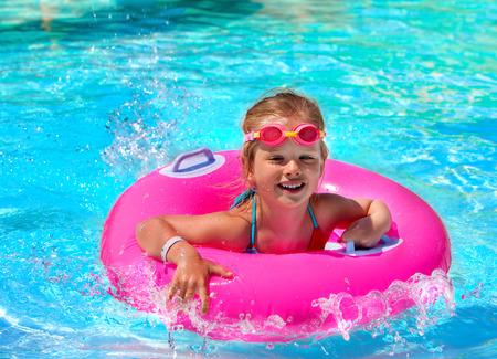 Enfants assis sur un anneau gonflable en piscine. Banque d'images