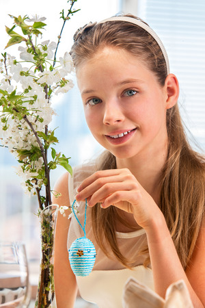 Child with long hair hang easter egg on cherry branch. Window in background photo