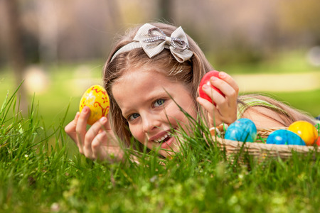 red sun: Happy child lying on green grass. and find easter egg outdoor. Stock Photo