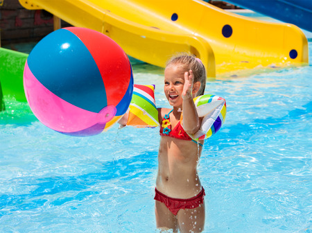 white beach: Child on water slide at aquapark. Girl playing beach ball. Summer holiday. Stock Photo