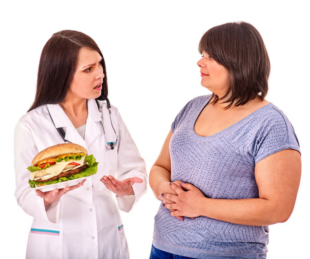 high calorie foods: Overweight woman with hamburger . Doctor forbids eating fast food.