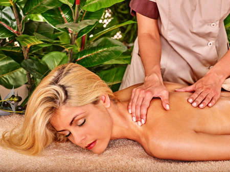 masseuse: Blond woman getting massage in tropical spa. Visible hand masseuse.
