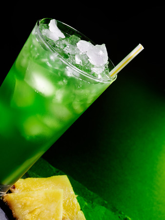 tilted view: Green drink  with straw and ice on dark background. Top view. Glass tilted Stock Photo