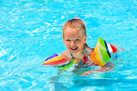 armbands: Child with armbands play in swimming pool. Summer outdoor.