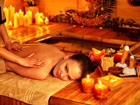 female therapist: Woman getting massage in bamboo spa. Female therapist.