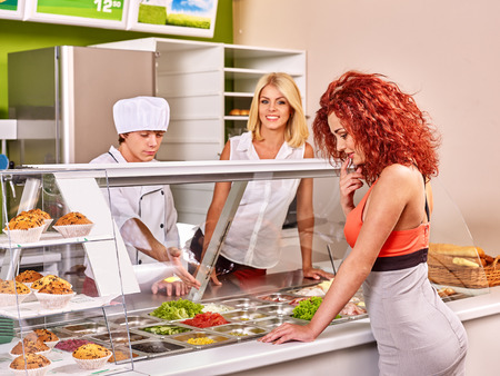 cafeteria tray: Women at cafeteria buying food. Seller man. Stock Photo