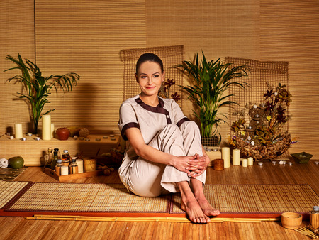 deportment: Bamboo massage at spa and woman. Sitting on floor. Stock Photo