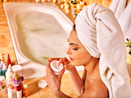 bathroom women: Woman applying moisturizer at bathroom. Towel on head. Stock Photo