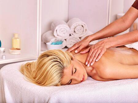 masseuse: Blond beautiful woman getting  back massage. Visible hand masseuse