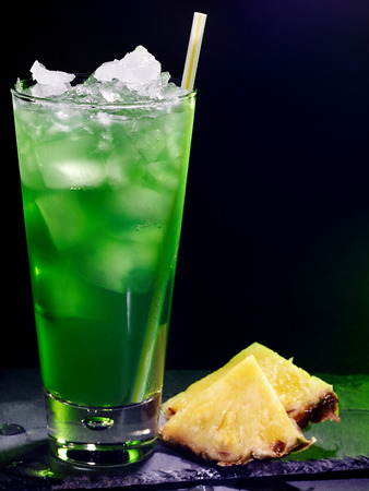 Green pine applee drink  with straw and ice cube on black background. Cocktail card 16.
