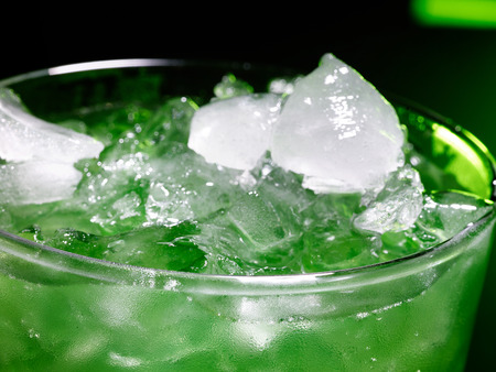 crushed ice: Green drink  with crushed ice on dark background. Top view.Close up.
