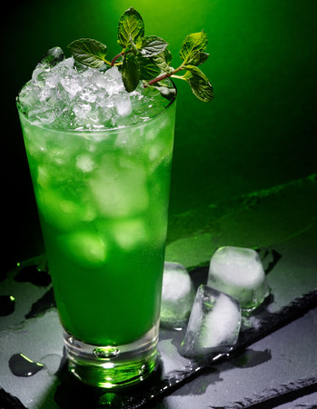 pilsner glass: Green drink  with cube ice and mint leaf on dark background.17