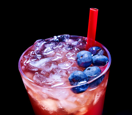 Cold red blueberry drink  with berry and straw. Top view. Close up. photo