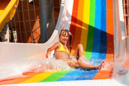 bikini wear: Girl in yellow bikini sliding water park.