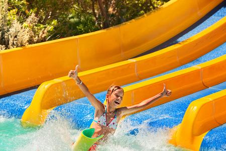 child in bikini: Happy child girl in bikini sliding water park. Stock Photo