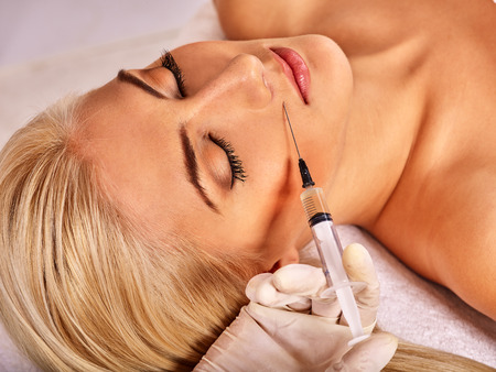 botox: Doctor woman giving botox injections. Visible hand. Stock Photo
