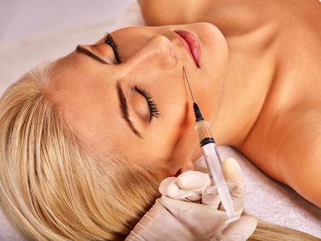 inyeccion: Mujer del doctor que da las inyecciones de botox. La mano visible.
